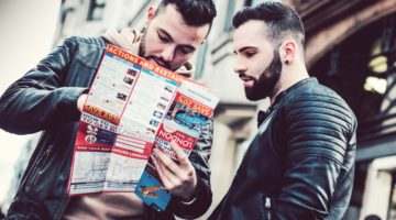 Feature   two men reading brochure   Must Have Travel Items For Men To Survive Your Next Holiday Getaway