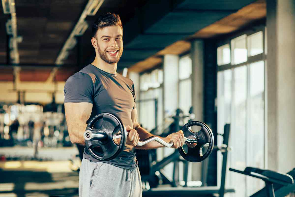 Handsome man doing biceps lifting in a gym | Ways To Reconnect With Your Manliness This New Year | become a better man